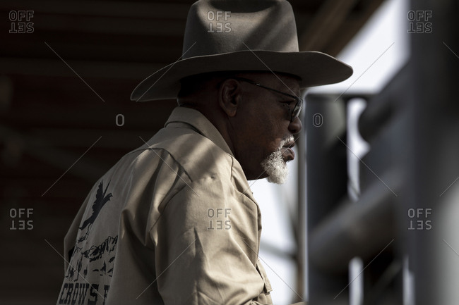 United States, Arizona, Chandler - March 9, 2019: A cowboy cast in light and shadow watches the Arizona Black Rodeo