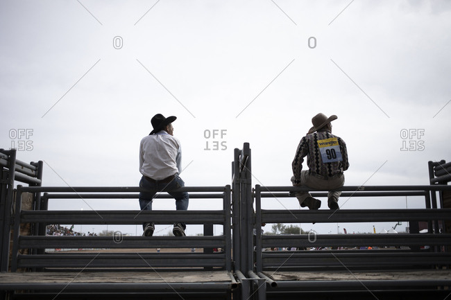 United States, Arizona, Chandler - March 9, 2019: Cowboys sitting on a fence at the Arizona Black Rodeo