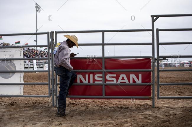 United States, Arizona, Chandler - March 9, 2019: A cowboy checks his phone at the Arizona black rodeo