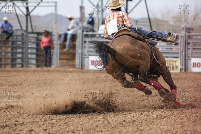 United States, Arizona, Chandler - March 9, 2019: A female rider competes in the barrel racing event at the black rodeo