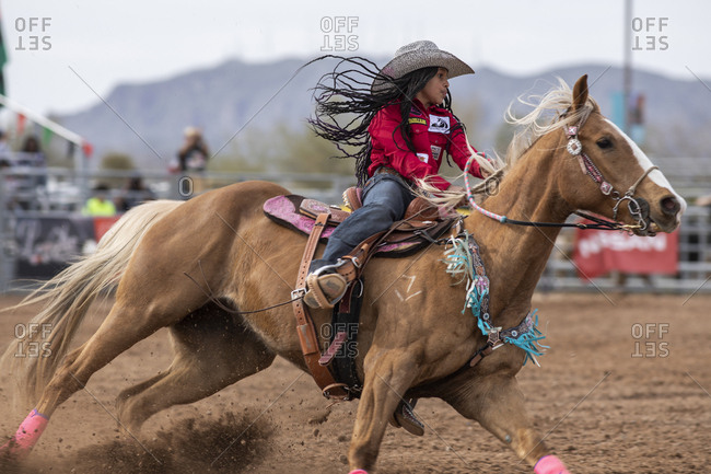 United States, Arizona, Chandler - March 9, 2019: A young woman rides in the barrel racing event at the AZ black rodeo