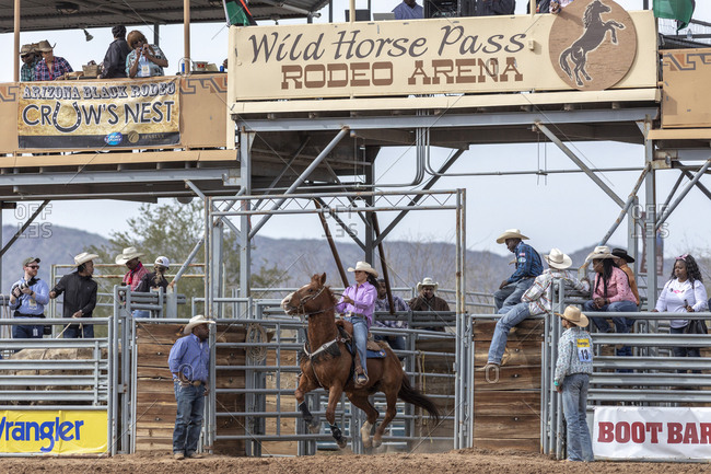 United States, Arizona, Chandler - March 9, 2019: A female rider blasts into the ring for the rodeo barrel racing event