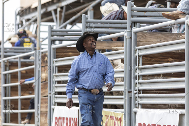 United States, Arizona, Chandler - March 9, 2019: A cowboy smiles up at some buddies in the stands at the rodeo