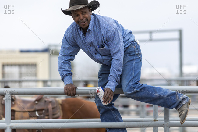 United States, Arizona, Chandler - March 9, 2019: A cowboy hops over a fence holding a can of beer at the Arizona black rodeo