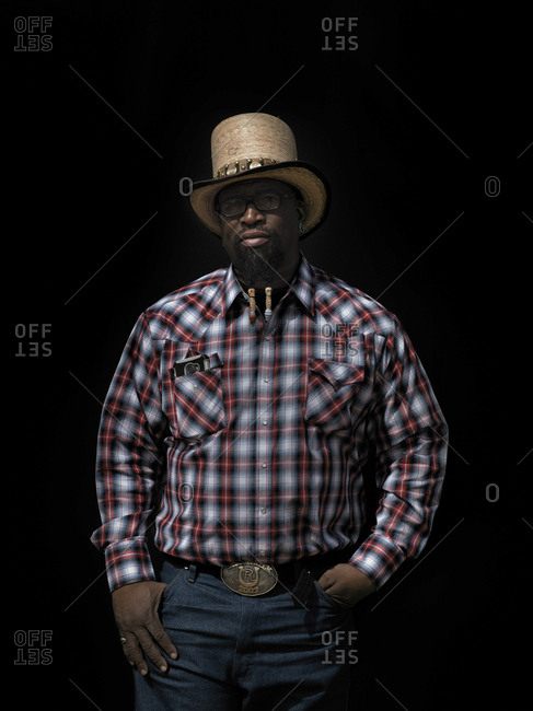 United States, Arizona, Chandler - March 9, 2019: A cowboy poses for a portrait against black in available sunlight