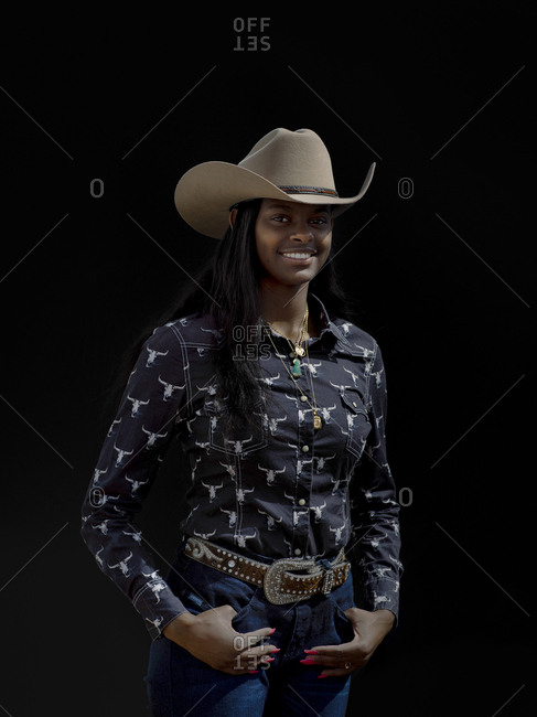 United States, Arizona, Chandler - March 9, 2019: A  rodeo cowgirl poses for a portrait against black in the daylight