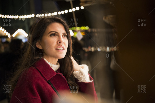 Portrait of young woman watching offers at Christmas market