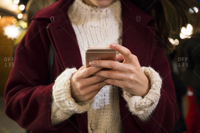 Hands of young woman holding smartphone- close-up