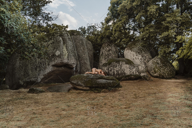 Nude woman lying on a rock at Beglik Tash prehistoric rock sanctuary- Bulgaria