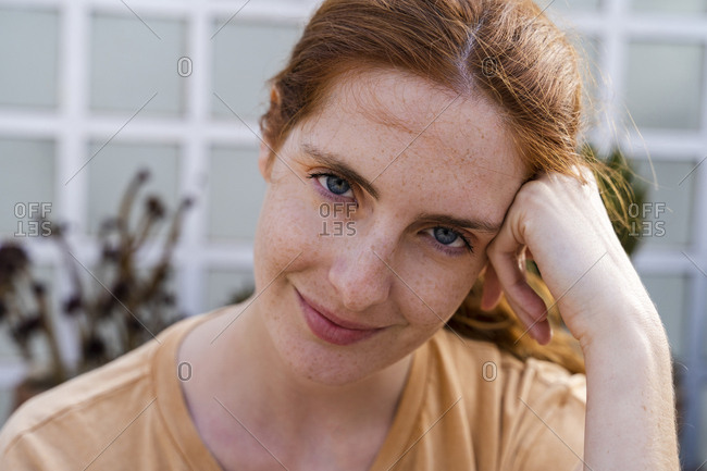 Portrait of smiling redheaded young woman with freckles
