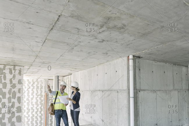 Male architect and female manager talking about architectural plan at construction site