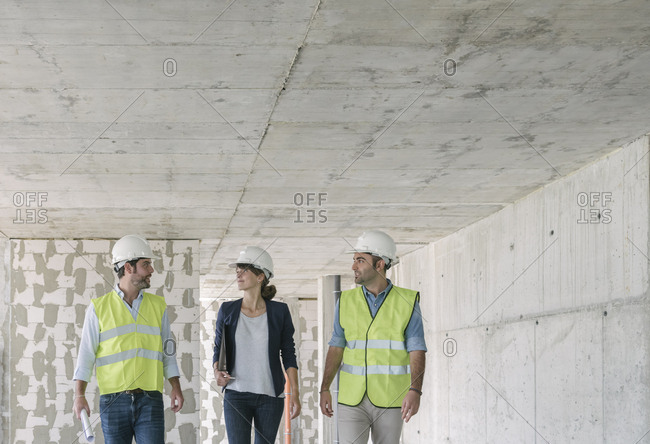 Male architects and female manager talking while walking at construction site