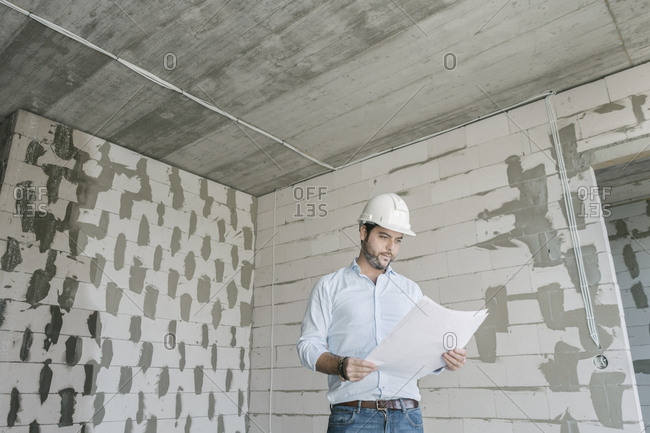 Architect checking architectural plan on construction site