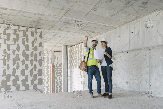 Male architect and female manager talking at construction site