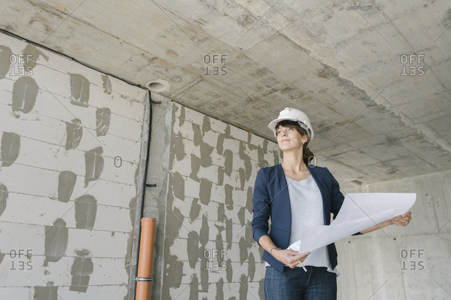 Female architect checking architectural plan on construction site