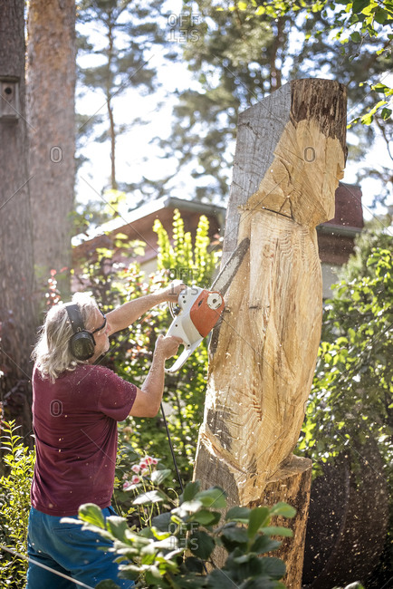 Wood carver carving sculpture- angel- using chainsaw