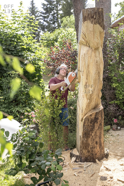 Wood carver carving sculpture- using chainsaw