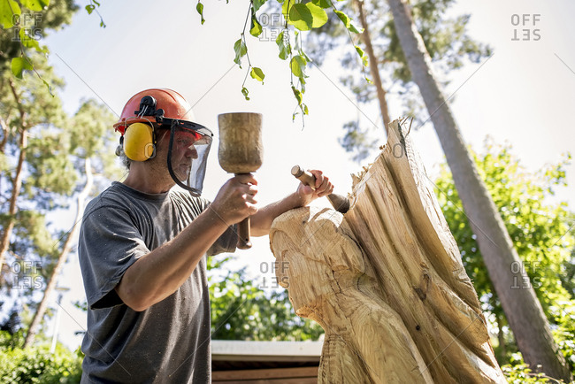 Wood carver carving sculpture- using chisel