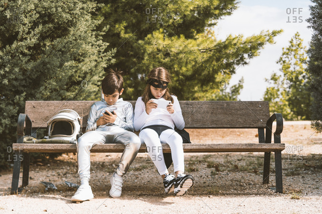 Two kids in astronaut and superhero costumes using mobile phone on park bench