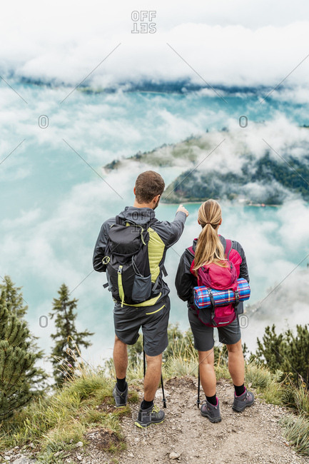 Young couple on a hiking trip in the mountains looking at view- Herzogstand- Bavaria- Germany