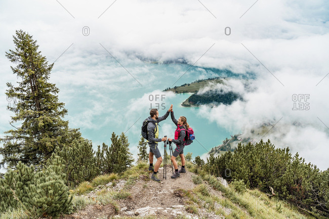 Happy young couple on a hiking trip in the mountains high fiving- Herzogstand- Bavaria- Germany
