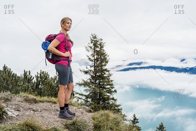 Young woman on a hiking trip in the mountains looking at view- Herzogstand- Bavaria- Germany