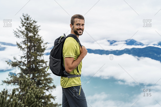 Portrait of smiling young man on a hiking trip in the mountains- Herzogstand- Bavaria- Germany