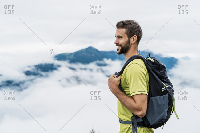 Smiling young man on a hiking trip in the mountains looking at view- Herzogstand- Bavaria- Germany