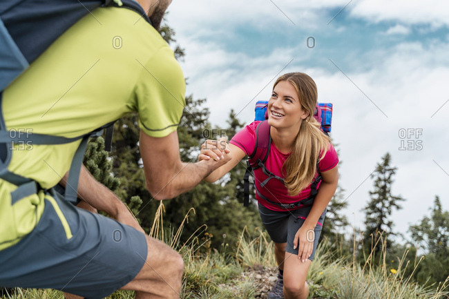 Young man helping girlfriend on a hiking trip in the mountains- Herzogstand- Bavaria- Germany