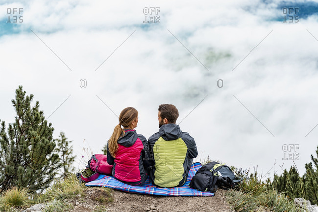 Young couple on a hiking trip in the mountains having a break- Herzogstand- Bavaria- Germany