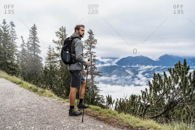Young man on a hiking trip in the mountains looking at view- Herzogstand- Bavaria- Germany