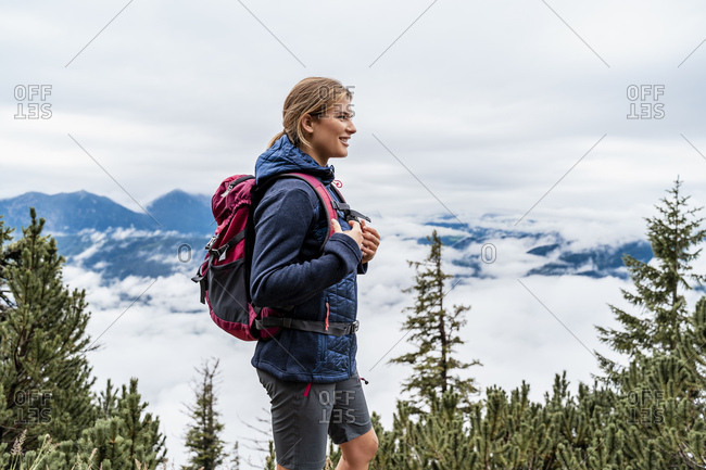 Smiling young woman on a hiking trip in the mountains- Herzogstand- Bavaria- Germany