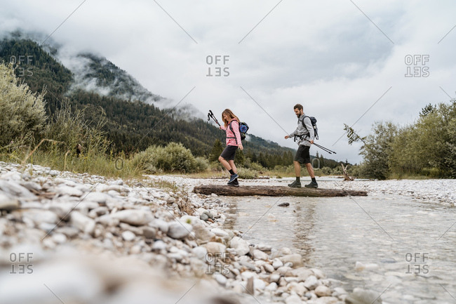 Young couple on a hiking trip crossing river on a log- Vorderriss- Bavaria- Germany