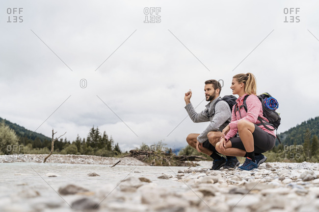 Young couple on a hiking trip crouching at riverside- Vorderriss- Bavaria- Germany