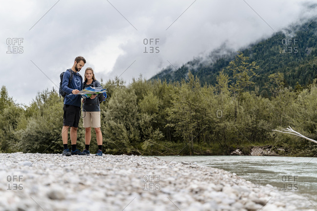 Young couple on a hiking trip at riverside reading map- Vorderriss- Bavaria- Germany
