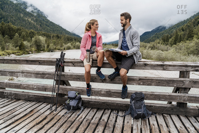 Young couple having a break on a wooden bridge during a hiking trip- Vorderriss- Bavaria- Germany