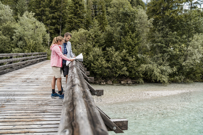 Young couple on a hiking trip reading map on wooden bridge- Vorderriss- Bavaria- Germany