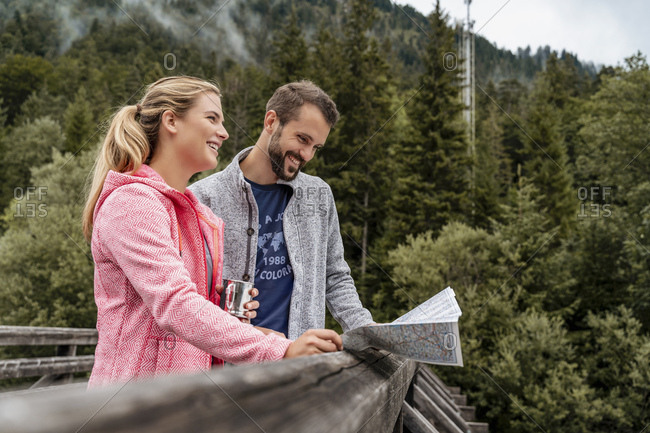 Happy young couple on a hiking trip reading map on wooden bridge- Vorderriss- Bavaria- Germany