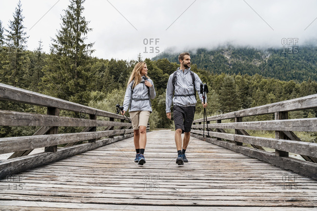 Young couple on a hiking trip walking on wooden bridge- Vorderriss- Bavaria- Germany