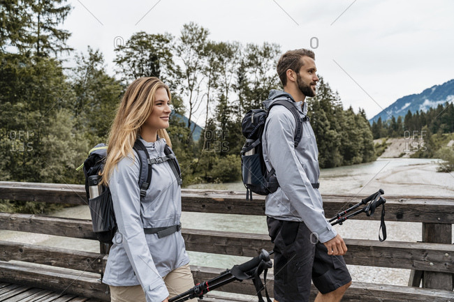 Confident young couple on a hiking trip walking on wooden bridge- Vorderriss- Bavaria- Germany