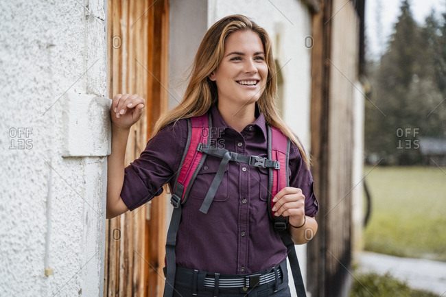 Smiling young woman at a farmhouse during a hiking trip- Vorderriss- Bavaria- Germany