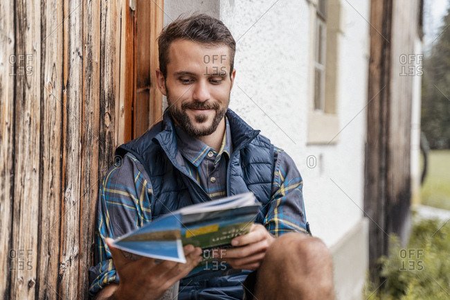Smiling young man with map at a farmhouse during a hiking trip- Vorderriss- Bavaria- Germany