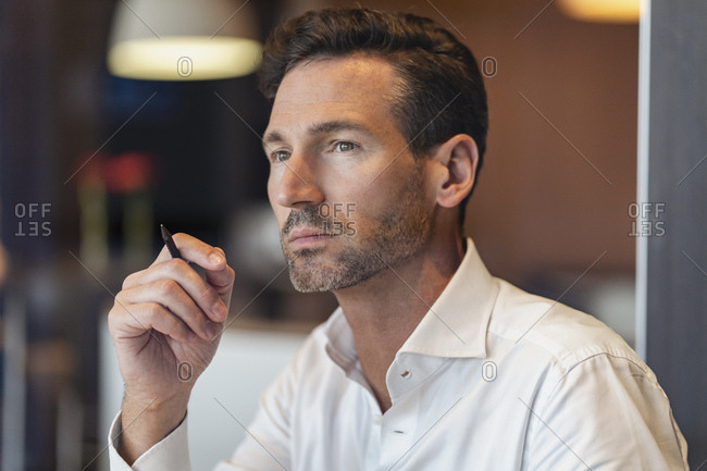 Portrait of thoughtful businessman holding pen