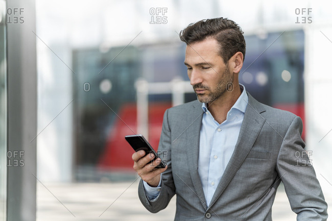 Businessman using cell phone in the city