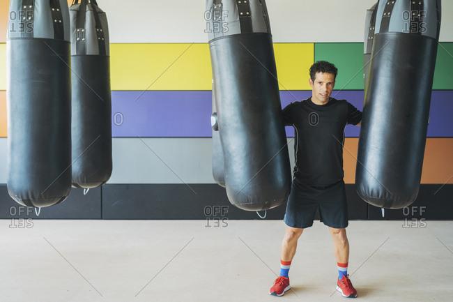 Portrait of man at sandbags in gym