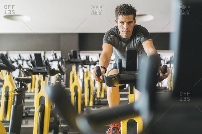Portrait of man in spinning class in gym