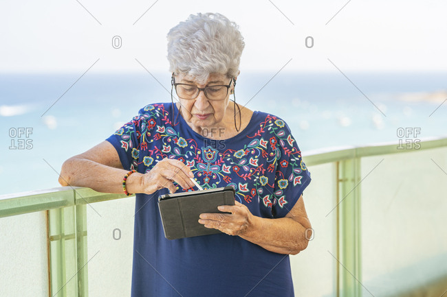 Senior woman using a tablet on a terrace