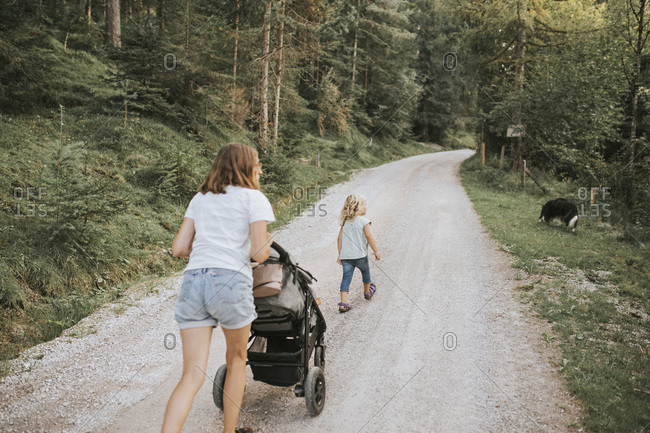 Mother with daughter- stroller and dog walking on forest path