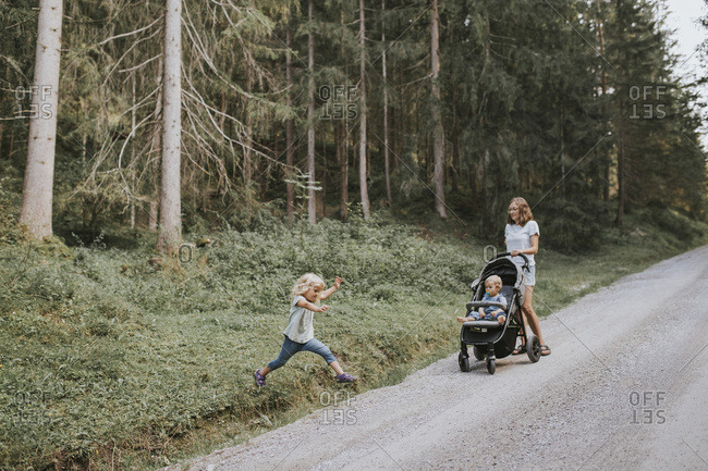 Mother with daughter and baby in stroller in forest
