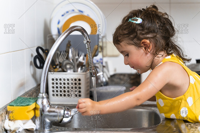 Little girl washing dishes in the kitchen tap at home